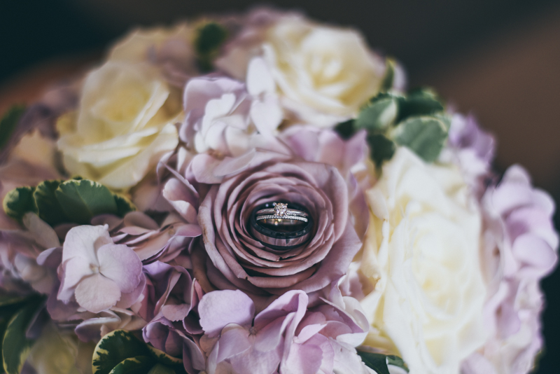 wedding bouquet with purple and ivory flowers and with the rings placed on a flower