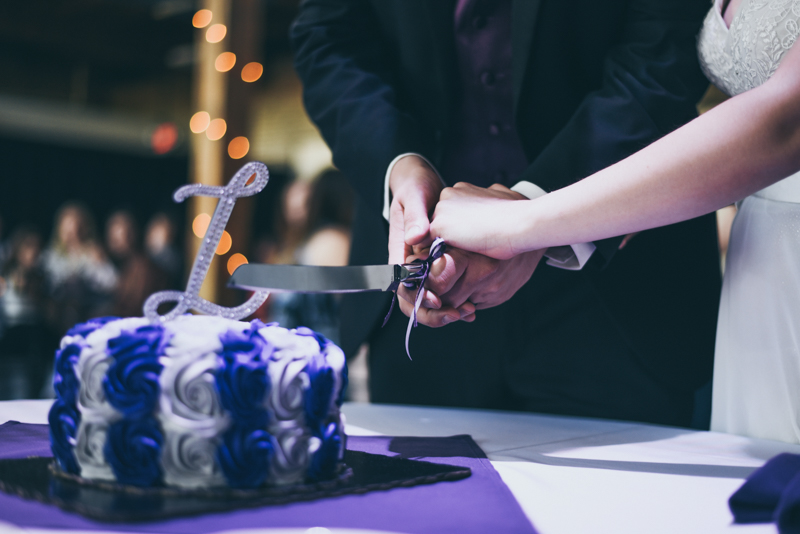 close up of bride and grooms hands while cutting cake