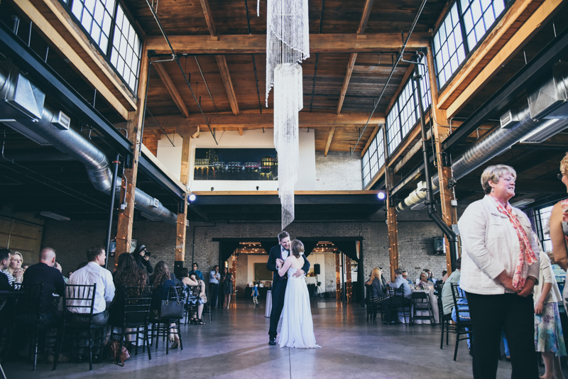 bride and grooms first dance under a crystal chandelier
