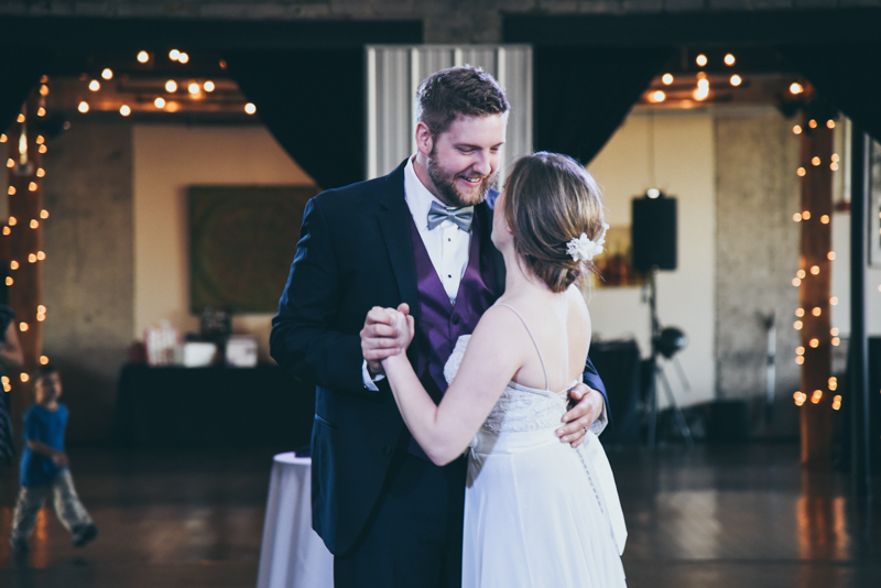 Bride and Groom's first dance under a crystal chandelier in an industrial loft wedding venue