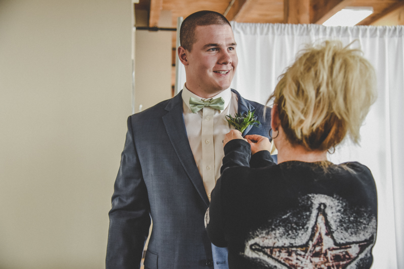 Image of a groom getting his flower pinned onto his jacket by a woman
