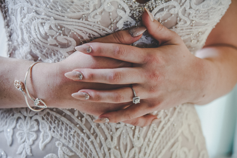 A brides pink manicured hands with engagement ring against a lace wedding dress