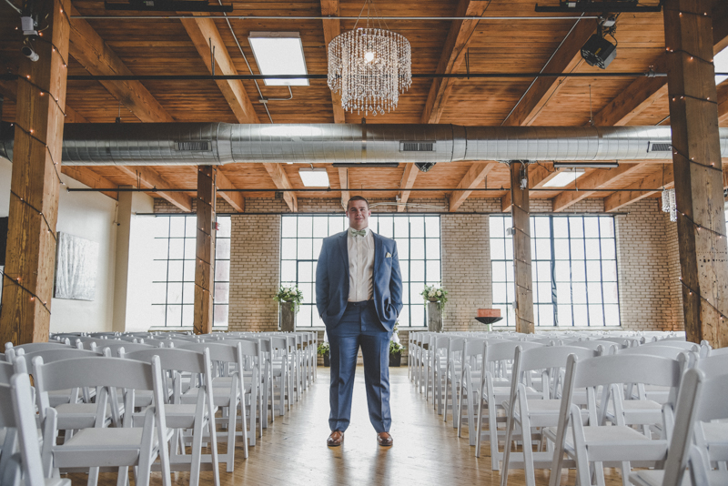 Groom standing in an aisle in an industrial loft venue with a wooden ceiling and beams above him