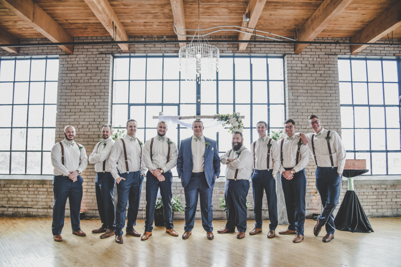 groom and groomsmen with jackets off in front of a large window in an industrial loft wedding venue