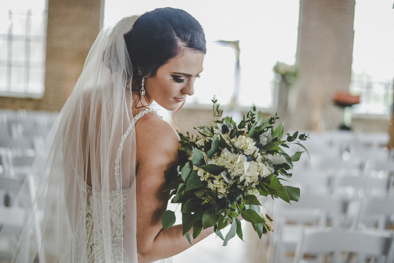 dark haired bride in a lace wedding dress with long veil looking down at a bouquet of white hydrangeas, greenery, and blue thistle