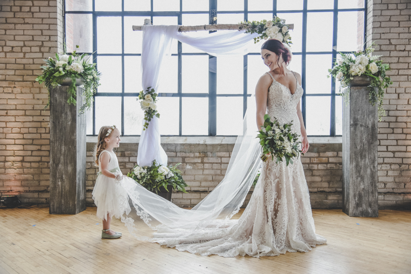 flowergirl holding the veil of a bride in a lace wedding dress while she looks back at her in front of a large window