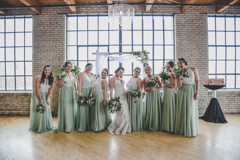 bride in lace wedding dress with bridesmaids in mint and lace dresses doing poses with lots of attitude