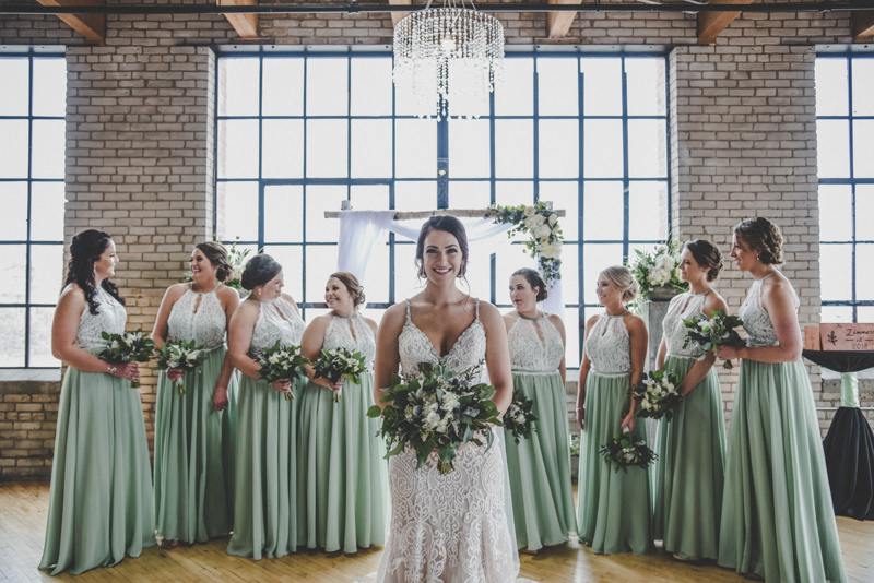 bride in a lace wedding dress standing in front of bridesmaids with mint dresses and lace accents while they chat