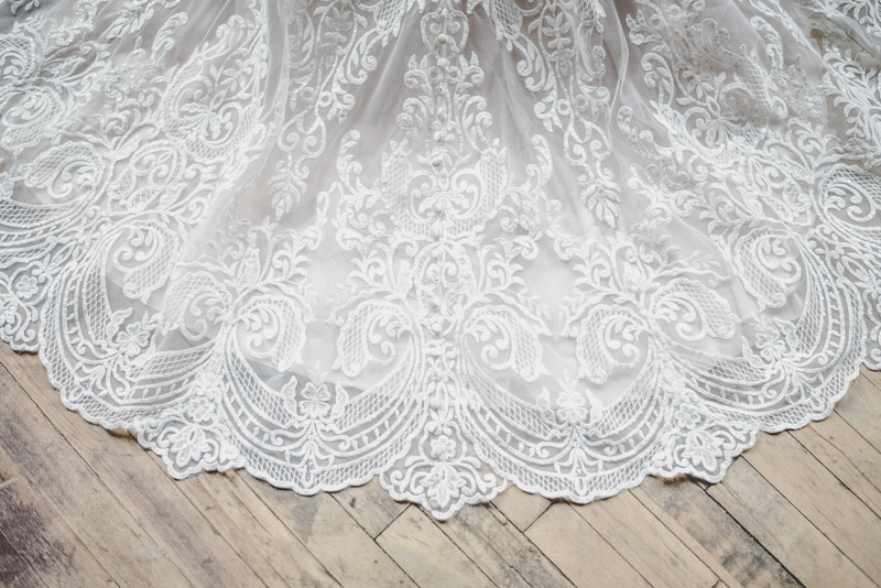 lace wedding dress against an old wooden floor