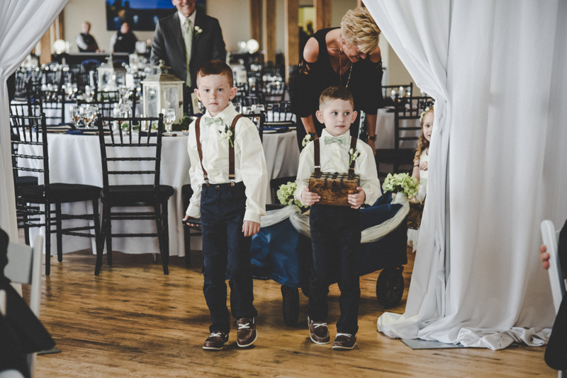 two little boys as ring bearers in dark pants and suspenders pulling a wagon with a baby flower girl