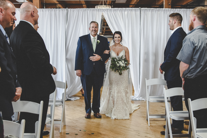 Father walking a daughter down the aisle in an industrial loft venue