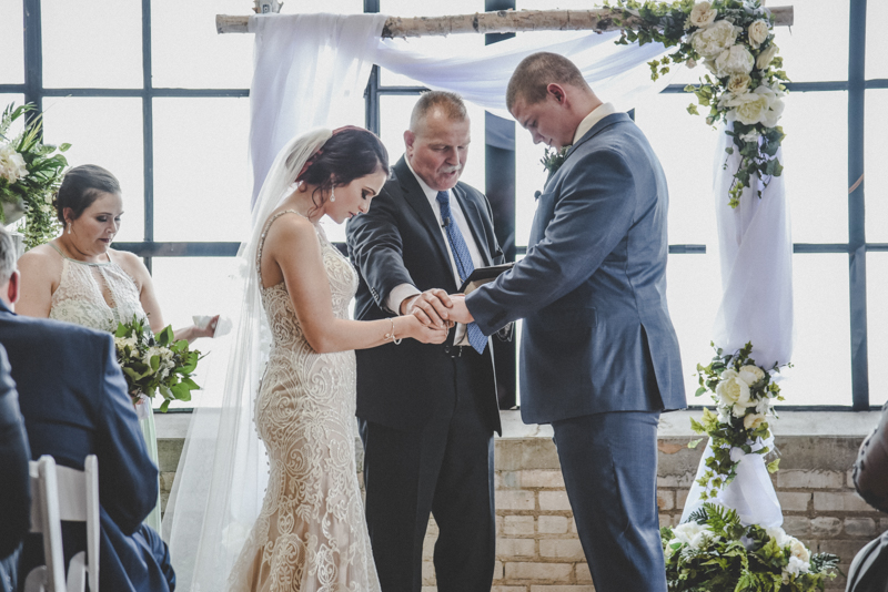 Minister praying over bride and groom at the altar