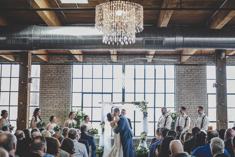 bride and groom first kiss under a crystal chandelier in an industrial loft venue
