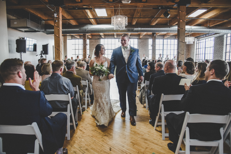 Smiling bride and groom walking down the aisle after being married in an industrial loft venue