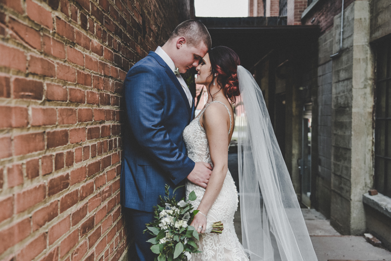 bride and groom touching foreheads together in a brick alley