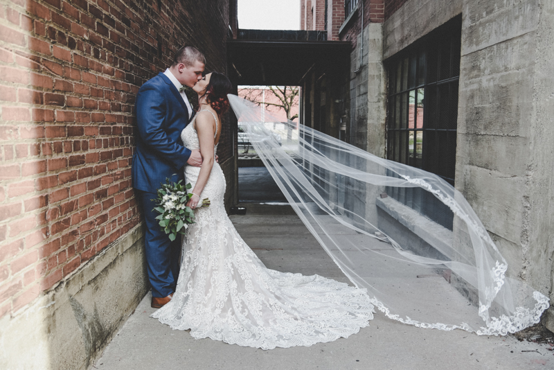 bride and groom kissing in an alley with her long veil blowing in the wind