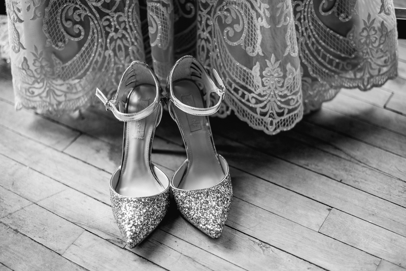 lace wedding dress and filigree silver wedding shoes against an old wooden floor