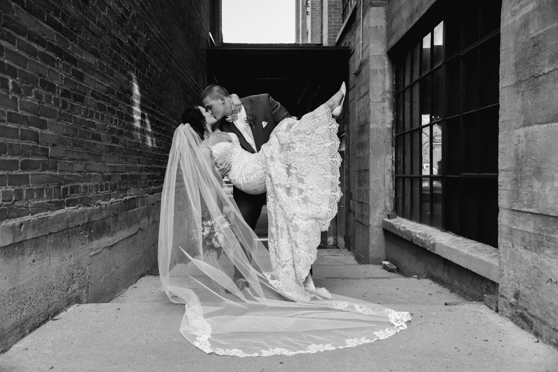a black and white image of a groom dipping his bride while kissing her in a brick alleyway