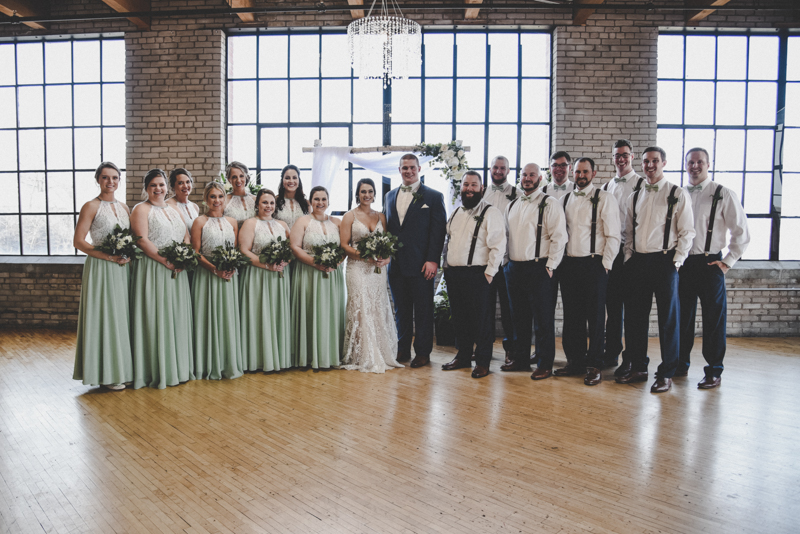 photo of bride, groom, and bridal party in an industrial loft venue