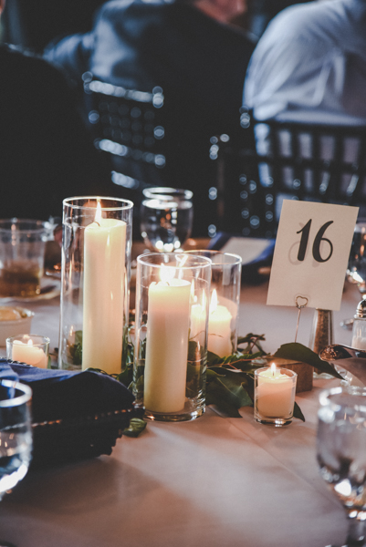 Wedding tablescape with lots of lit candles and greenery