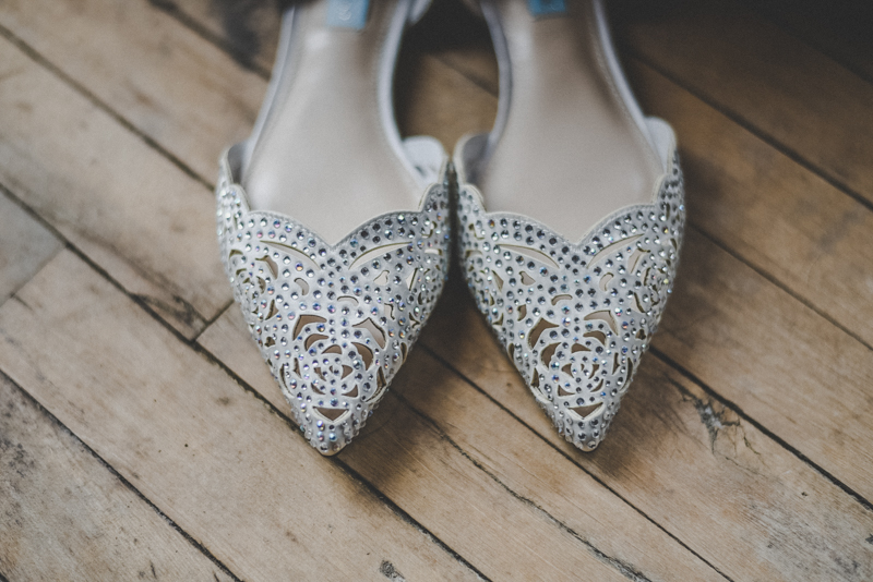 Filigree silver wedding shoes against an old wooden floor