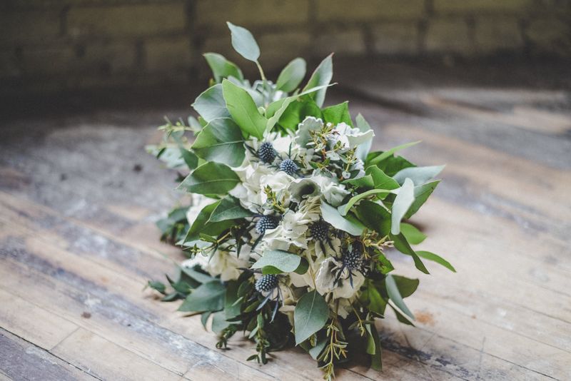 A wedding bouquet of white hydrangeas, greenery and blue thistle against an old wooden floor