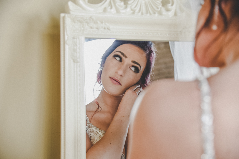A dark haired bride looking into a mirror and putting on her earrings