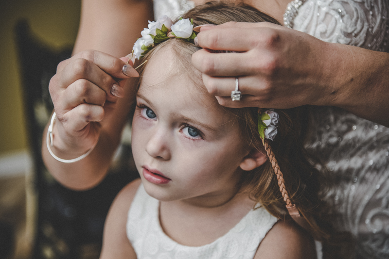 a blond flowergirl getting a flower crown placed on her head for a wedding