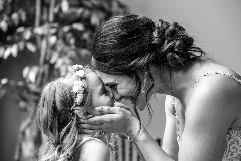 A dark haired bride holding the face of her blond flowergirl and laughing as they look into each others eyes