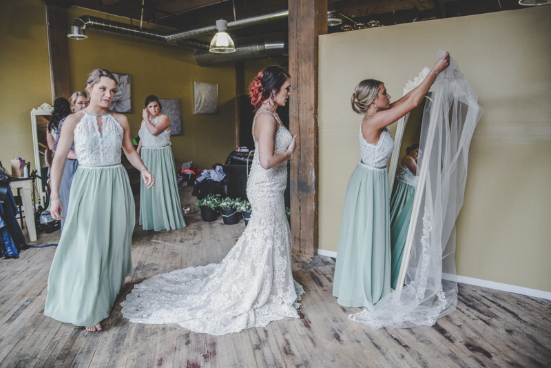 bridesmaids in mint and lace gowns helping a bride in a lace gown put on her cathedral veil in an old brick building