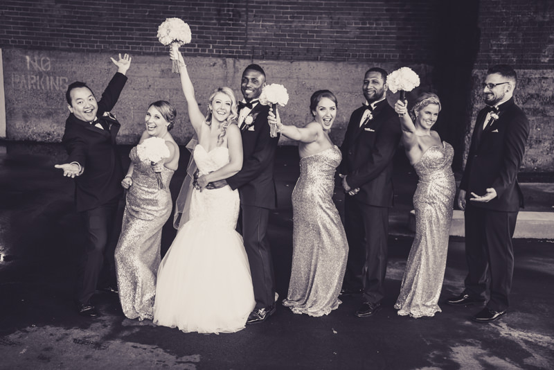 Black and white image of a fun bridal party against a parking garage exterior