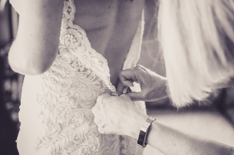 black and white image of a mother fastening her daughters wedding gown