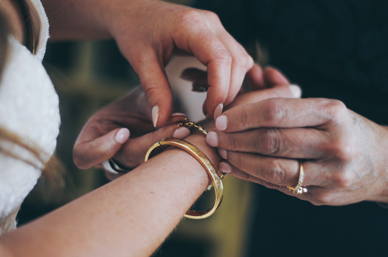 mother and daughters hands as they put a bracelet on the daughter for her wedding