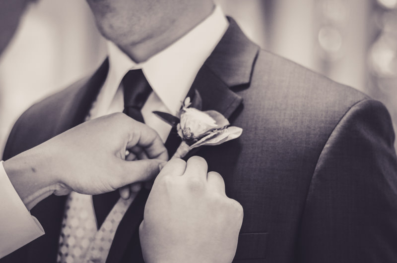 groomsman helping to pin flower on groom in church