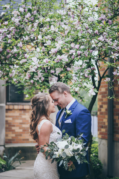 bride and groom kissing under a blossoming magnolia tree