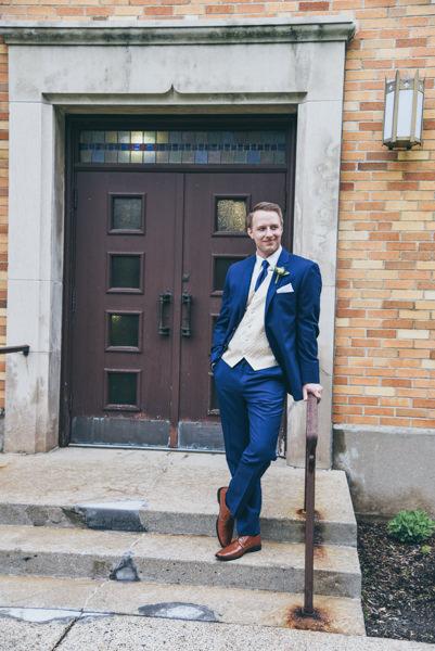 groom leaning on iron railing near church doors