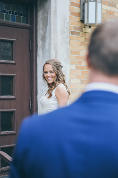 bride peeking over groom's shoulder in front of church doors