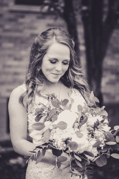black and white image of a bride looking down at her bouquet