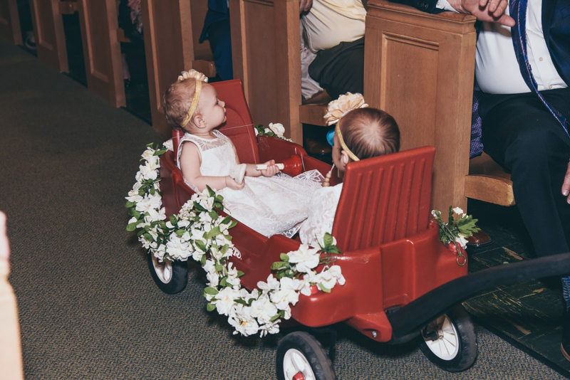 little flower girls being pulled in a decorated red wagon down the aisle