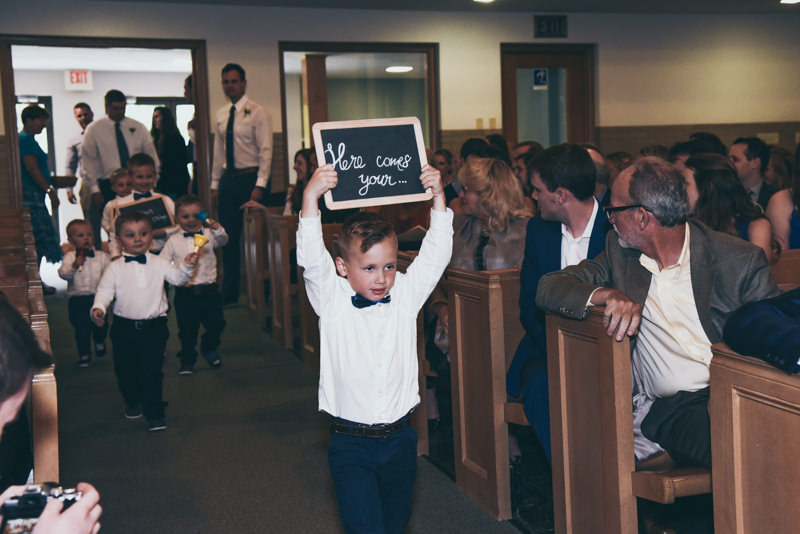 ring bearer holding a sign while walking down the aisle