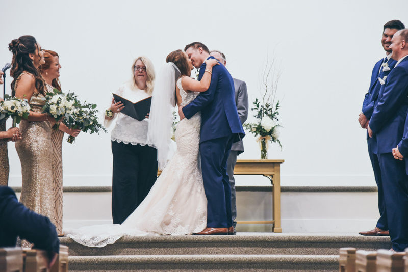 bride and groom having first kiss