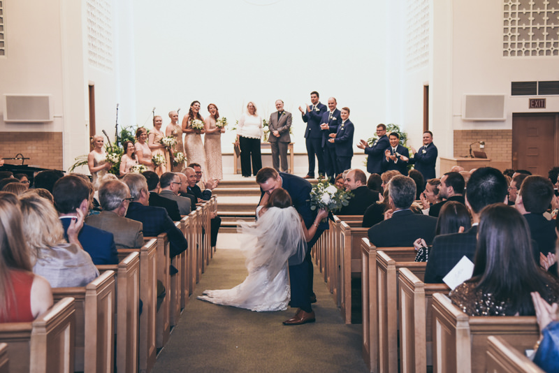 groom dipping bride and kissing her in the middle of the aisle
