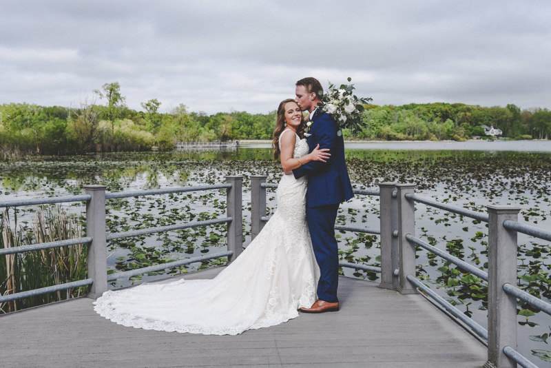bride and groom standing at a railing overlooking a pond