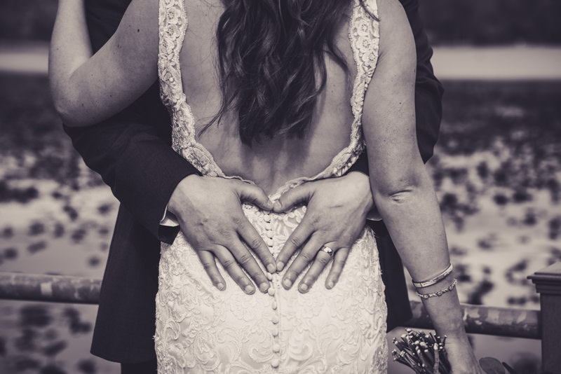 black and white image of a grooms hands making a heart on his brides back
