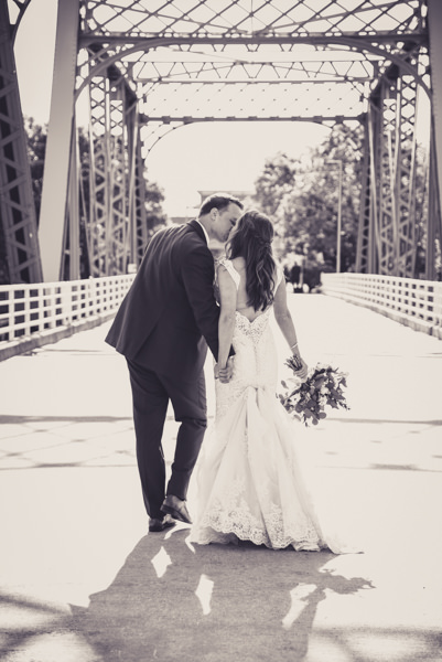 black and white photo of a bride and groom kissing on a blue bridge