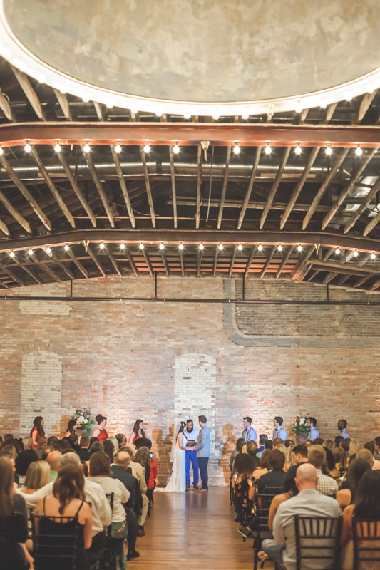 image of bride and groom and bridal party in front of the altar in a brick building