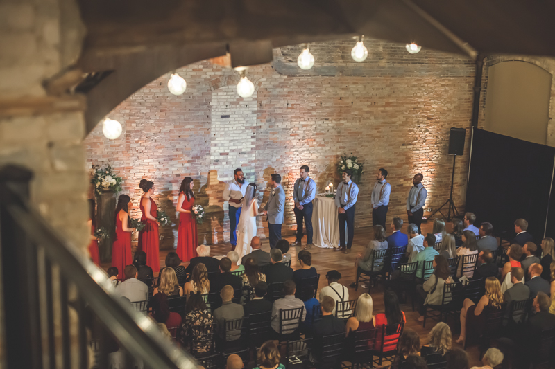 looking at a wedding ceremony from a balcony with marquis bulbs