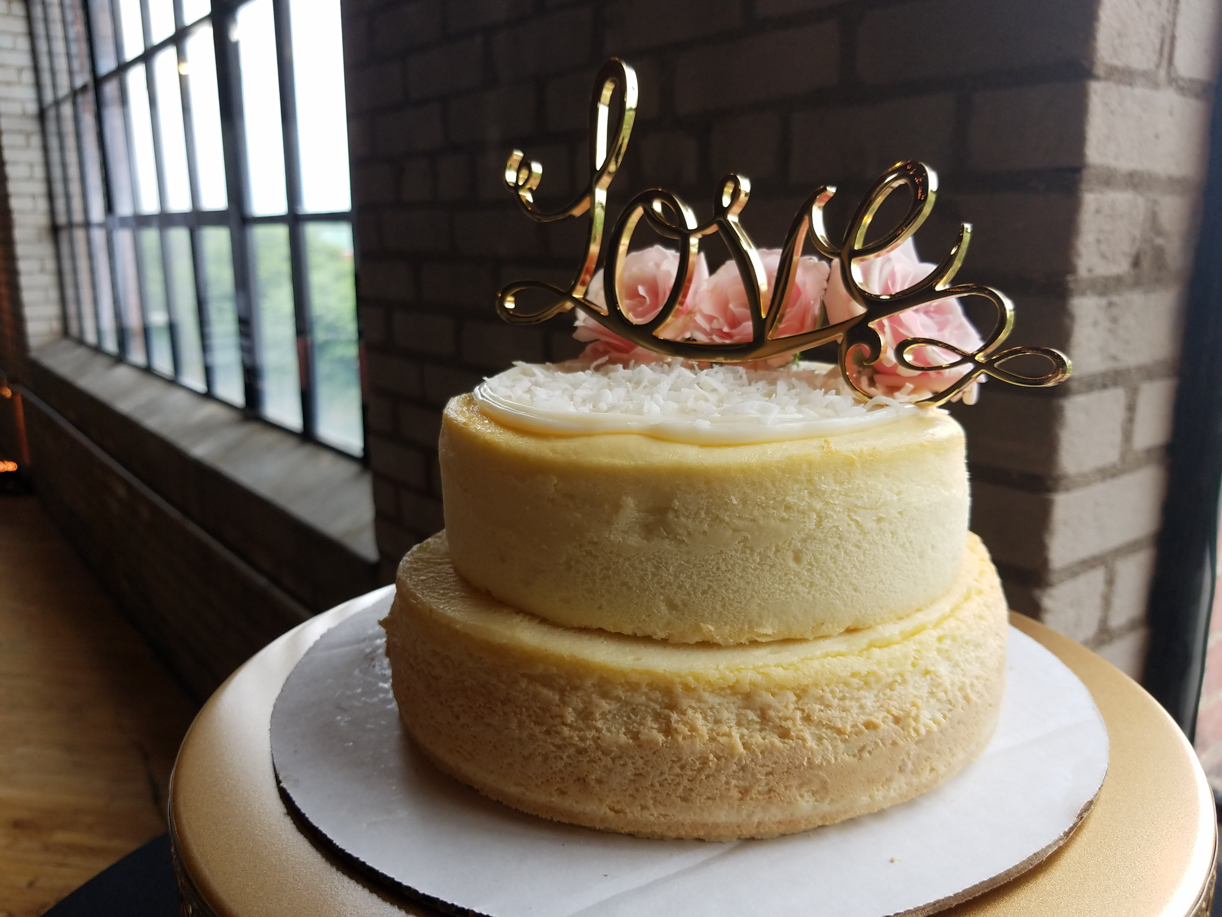 tiered cheesecake wedding cake with gold love sign