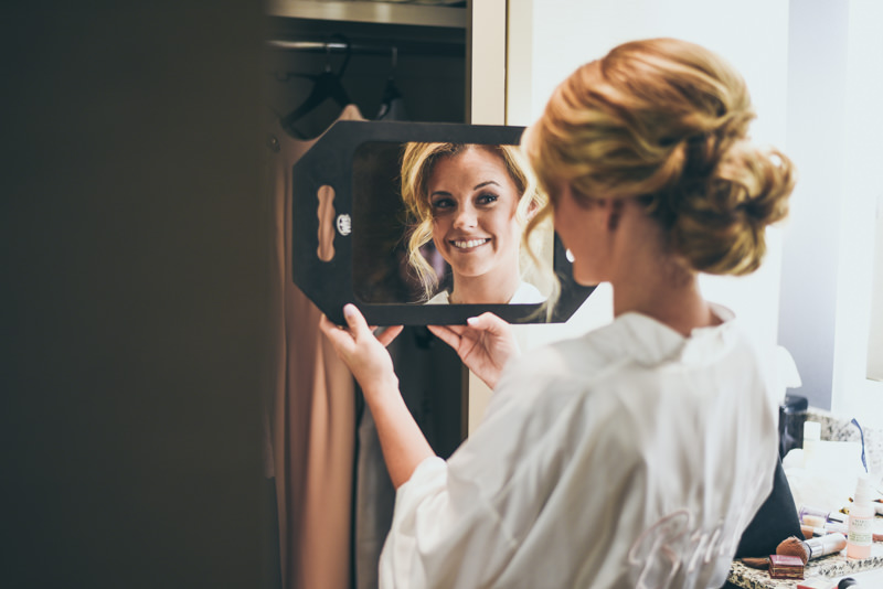 bride smiling as she looks into a mirror after getting her hair done