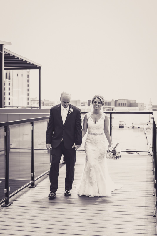 black and white image of a bride and groom walking on a city building roof